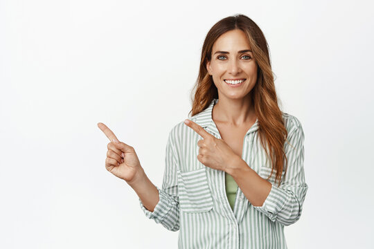 Image of confident, ambitious middle aged woman smiling white teeth, pointing fingers left at logo, copyspace for your advertisement, place your text here, studio background