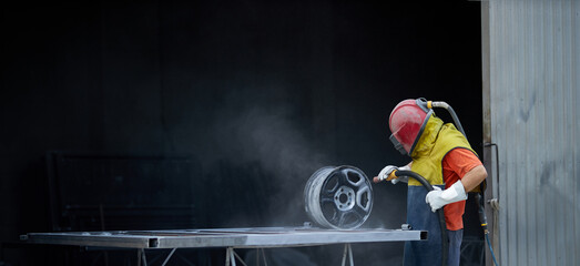 Fototapeta Caucasian man dressed in special protective equipment using sandblaster for cleaning metal details at work. Concept of people and repairing. obraz