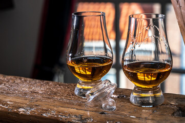 Fototapeta Dram of single malt scotch whisky served in tasting glass with view on old window and houses obraz