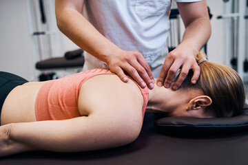 Fototapeta Young woman getting neck, head massage in therapy room. Masseur making chiropractic treatment obraz