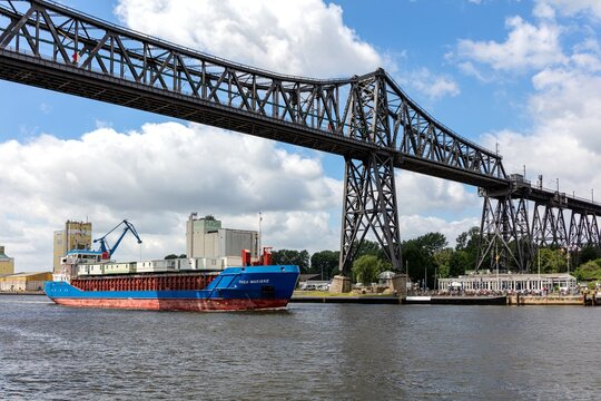 RENDSBURG, GERMANY - JUNE 13, 2021: General cargo vessel THEA MARIEKE in the Kiel Canal passing the Rendsburg High Bridge and the ships welcome point.