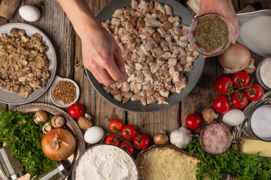 A beautiful composition of vegetables, herbs and other ingredients. The cook fries mushrooms for pizza. He adds spices to the pan where the mushrooms are cooked.