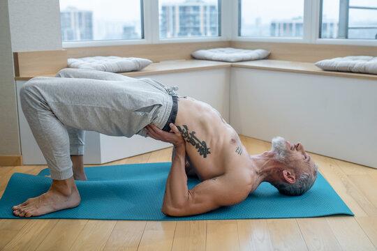 A mature yogi exercising at home and doing difficults asana.