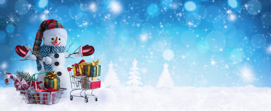 Happy snowman in warm clothes, red mittens, hat and scarf with basket and shopping trolley in winter scenery. Winter or Christmas Panoramic background.