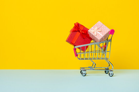 Toy shopping cart or trolley with full with gift boxes. A gift for a holiday, anniversary or birthday. Trolley cart with gift boxes Isolated over yellow background.
