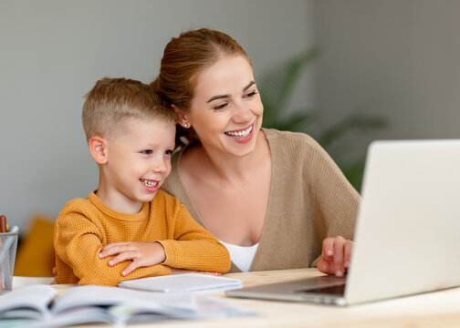 Happy mother supporting son during online studies