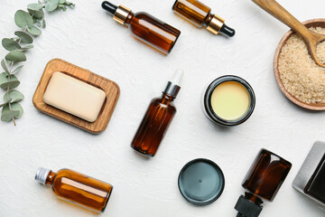 Different cosmetic products and sea salt on light background