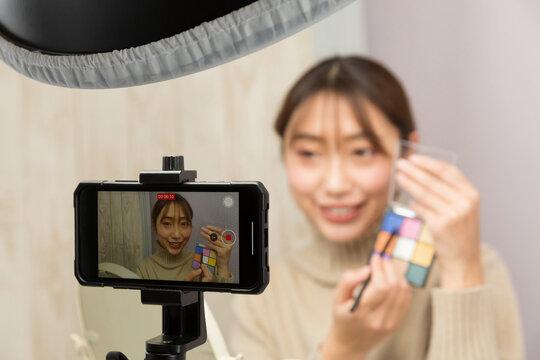 スマートフォンでメイクの動画を撮影する女性