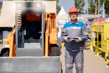 Fototapeta Senior worker forklift driver checks route plan on tablet computer. Concept of online internet technologies in construction obraz