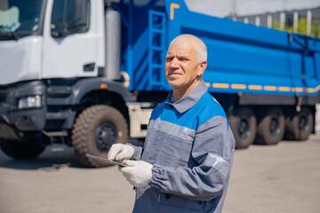 Fototapeta Dump truck driver man in uniform with tablet computer controls loading of cargo or coal. Concept automated logistics online internet obraz