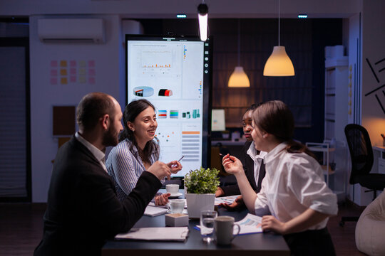 Diverse multi-ethnic businesspeople analyzing management strategy working overtime in company office meeting room late at night. Overworked leader overworking marketing strategy in evening
