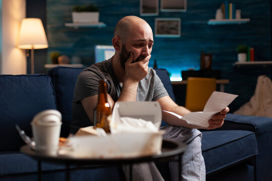 Desperate frustrated stressed young man reading letter, payment debt notification, bad financial report, eviction renter notice. Anxious, worried tenant by warning document for unpaid bank bills