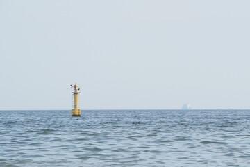 Fototapeta Boja i wielki statek daleko na horyzoncie obraz
