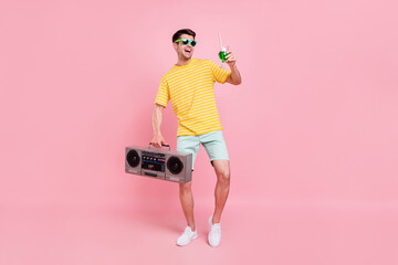 Fototapeta Full body photo of cheerful young happy man hold hand boombox cocktail look empty space isolated on pink color background obraz