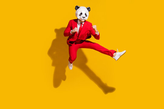 Photo of kung-fu panda guy jump hold fists kick leg empty space wear mask red tux shoes isolated on yellow color background