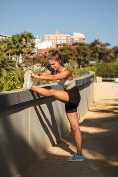 Caucasian adult girl runner stretching for muscle cramp
