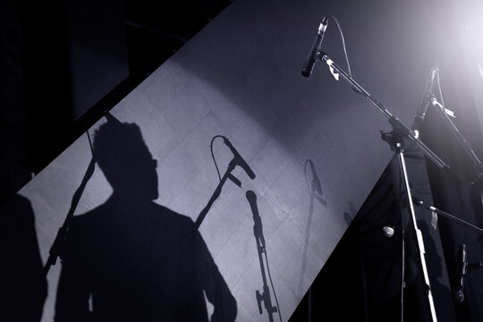 Silhouette of a male moderator or presenter and a professional speech or presentation on stage with a microphone.