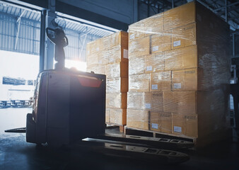 Obraz Stacked of Package Boxes with Electric Forklift Pallet Jack at The Storage Warehouse. Shipping Warehouse Logistics. - fototapety do salonu