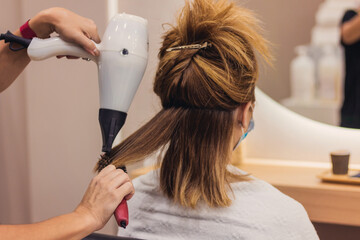 woman with face mask getting blow dry in hair salon