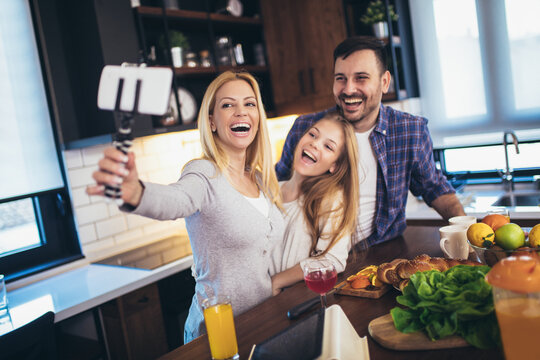Girl and her beautiful parents are cutting vegetables and smiling while cooking in kitchen at home make selfie photo.