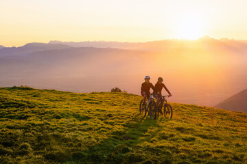 Mother and daughter cycling on mountain bikes at a sunset in mountains.