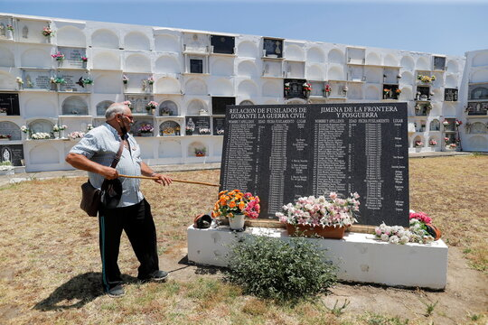 Enrique Rojas stands next to a memorial stone with the names of people killed during the Spanish Civil War during an exhumation of mass graves at a cemetery in Jimena de la Frontera