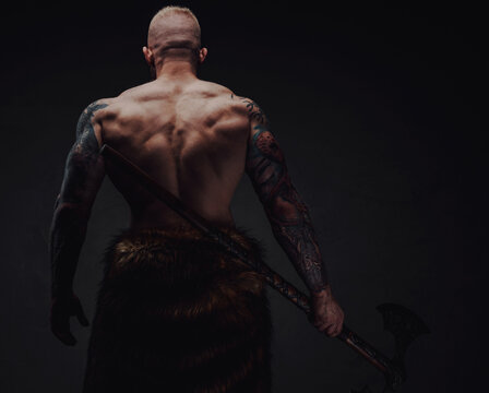 Rear view of healthy tattoed warrior in fur with axe on a dark background