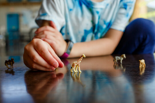 close-up of little girl playing with miniature toy animals on tabletop