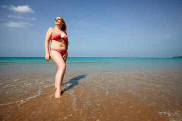Obraz Full body of smiling overweight woman covering face from sunlight while standing on sandy beach near waving sea - fototapety do salonu