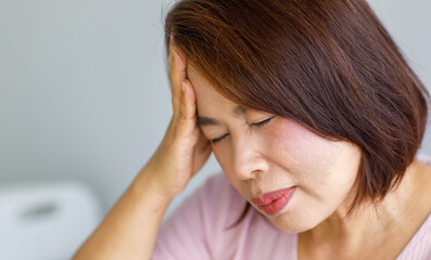 Fototapeta Middle age senior Asian woman feeling pain from sudden headache and brain stroke attack and hold her head with a stressed face. Concept of brain and head problem obraz