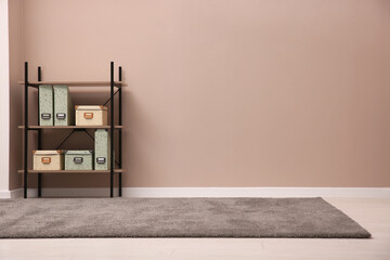 Fototapeta Room with soft grey carpet, shelving rack and pale brown wall. Space for text obraz