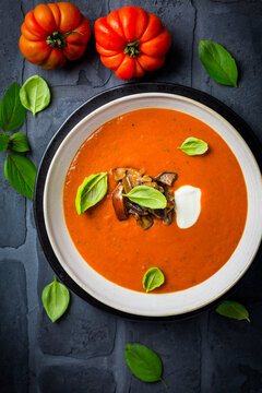Homemade tomato soup with roasted eggplant and basil