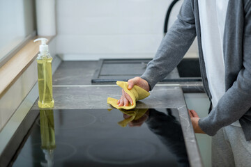 Fototapeta Close up picture of a man cleaning the surface of the table in the kitchen obraz