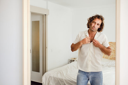 Handsome man buttoning shirt in room