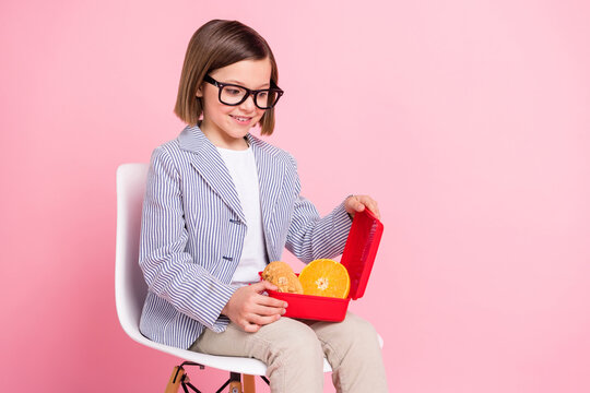 Portrait of attractive cheerful girl sitting in chair eating tasty yummy fresh homemade lunch box isolated over pink pastel color background
