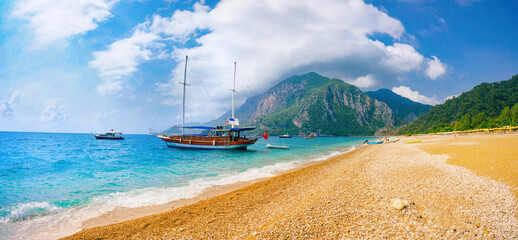 Fototapeta Beautiful panoramic view of sea and beach Cirali, Kemer, Antalya, Turkey. Ship against backdrop of mountains and blue sky with clouds on sunny day. obraz