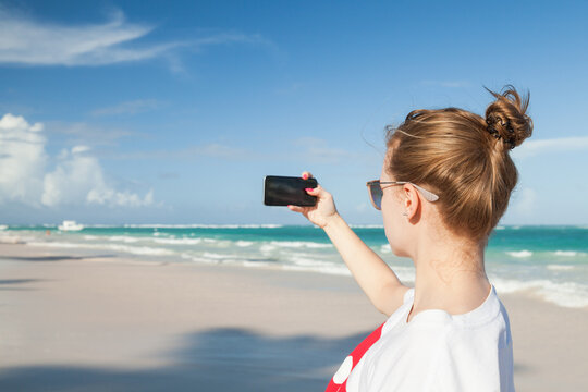 Young girl in white t-shirt takes seascape photo