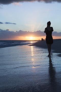 A girl walks the ocean coast in the sunrise