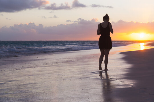 Silhouette photo of a girl walking at the Atlantic Ocean coast