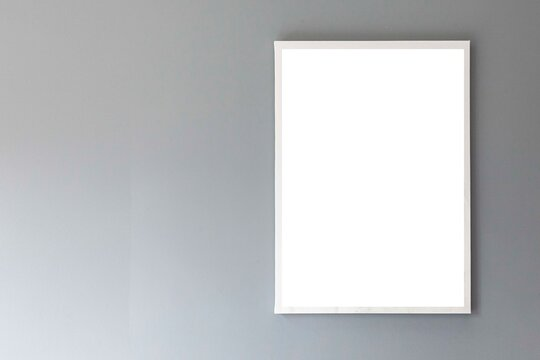 Blank white photo frame on a smooth gray wall