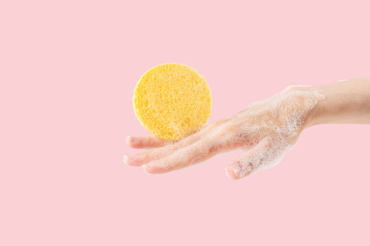 Hand of an anonymous woman with foam and a yellow sponge