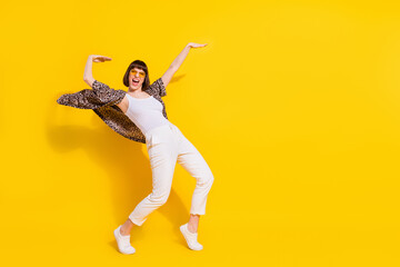 Full length photo of crazy lady dance arm up wear eyewear shirt trousers sneakers isolated on yellow color background Wall mural