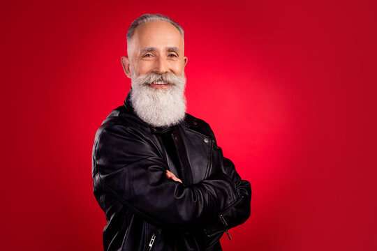 Profile side view portrait of attractive cheerful modern grey-haired man folded arms isolated over bright red color background