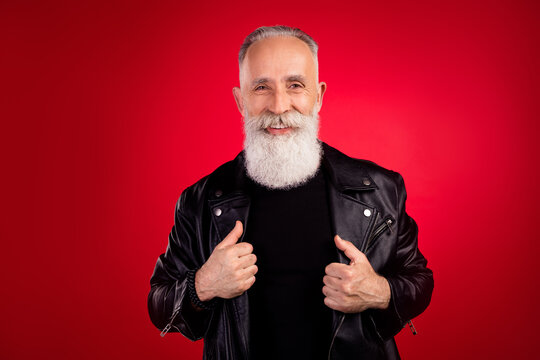 Portrait of attractive cheerful fashionable grey-haired man wearing cool jacket isolated over bright red color background