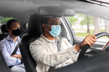 Fototapeta transportation, health and people concept - indian male taxi driver driving car with passenger wearing face protective medical mask for protection from virus disease obraz