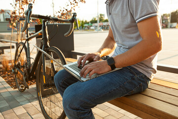 Fototapeta Young man working on laptop a while sitting on the bench near his bicycle obraz