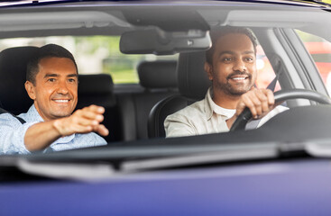 driver courses and people concept - happy smiling car driving school instructor teaching young man...