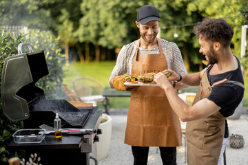 Fototapeta Two handsome male friends have fun while grilling meat and buns for burgers on gas grill at backyard on nature obraz
