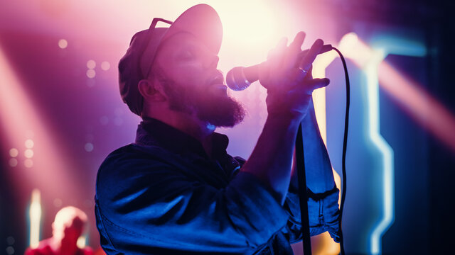 Rock Band Performing at a Concert in a Night Club. Portrait of a Lead Singer Singing into Microphone. Live Music Party in Front of Bright Colorful Strobing Lights on Stage.