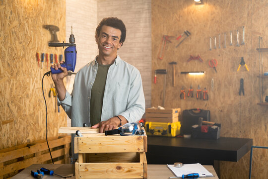 Portrait of a smiling carpenter in workshop with a drill